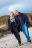 Mature senior couple walking on the beach autumn winter Stock Image