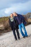 Mature senior couple walking on the beach autumn winter Royalty Free Stock Images
