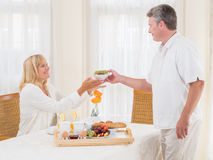 Mature senior husband serving his wife healthy breakfast. Passing her a bowl of cereal off the tray laden with fresh fruit, eggs, baguette and coffee as she Stock Image