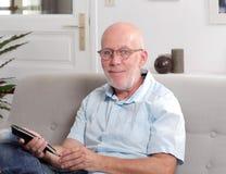 Mature senior man with blue shirt watching tv. A mature senior man with blue shirt watching tv Royalty Free Stock Photos