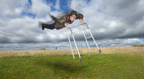 Mature Senior Man Fly in Sky With Walker, Young at Heart. Concept for aging and elderly living a full life and feeling young at heart. A mature senior man flies Royalty Free Stock Photo