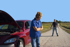 Mature Senior Woman Car Trouble, Danger Man Safety. Scene depicts a mature senior woman with car trouble and confronts a scary criminal man on a lonely back road Stock Photo
