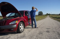 Mature Senior Woman Car Trouble, Road Breakdown. Mature senior female woman with car broke down and in trouble. The hood is popped up as a signal of distress but Royalty Free Stock Image