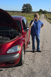Mature Senior Woman Car Trouble, Road Breakdown. Mature senior female woman with a car broke down and in trouble. The hood is popped up as a signal of distress Royalty Free Stock Images