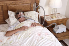 Mature Senior Woman CPAP Sleep Apnea Machine. Mature senior woman with CPAP sleep apnea machine lying on bed in bedroom. Used by people with sleeping disorders Stock Photo