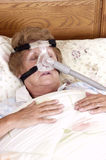 Mature Senior Woman CPAP Sleep Apnea Machine. Mature senior woman with CPAP sleep apnea machine lying on bed in bedroom. Used by people with sleeping disorders royalty free stock image