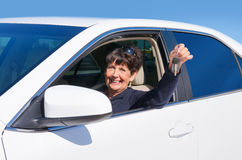 Mature elderly senior woman driver smiling w new car keys. A very happy mature senior woman driver smiling and holding out the keys to her beautiful new car Stock Photography