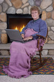 Mature Senior Woman Laptop Computer by Fireplace royalty free stock images