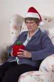 Mature Senior Woman Mad Angry Christmas Present. Funny, humorous scene of a mature senior woman who is mad, angry, and upset with a Christmas present gift box Stock Photo