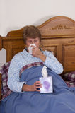 Mature Senior Woman Sick Bed, Sniffles, Allergies. Mature senior woman is sick in bed with a runny nose and sniffles. Grandma is using tissues to help her Stock Image
