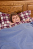 Mature Senior Woman Smiling Happy in Bed. Mature senior woman is smiling and happy in bed. It's nap time for grandma as she lays back on the pillow and covers up Stock Photos