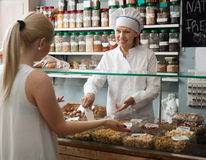 Mature shop woman offering client nuts and smiling. Cheerful mature shop women offering client nuts and smiling stock photography