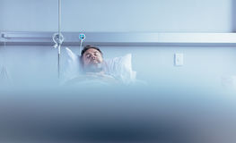 Mature sick male patient sleeping in hospital bed. Patient waiting for his health recovery in hospital ward Royalty Free Stock Images