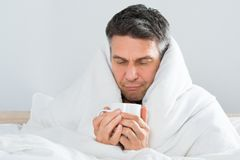 Mature sick man holding cup of coffee Stock Photography