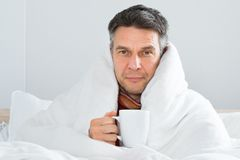 Mature sick man holding cup of coffee Royalty Free Stock Photo