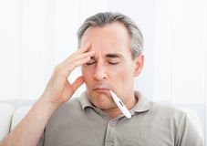 Mature sick man with a thermometer in his mouth Royalty Free Stock Photography