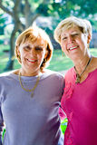 Mature sisters & friends. Portrait of two senior caucasian elegant women pose in the park on a sunny day. they are sisters and best friends stock photography