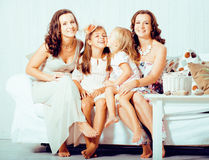 Mature sisters twins at home with little cute daughter, happy real family smiling together, lifestyle people concept Stock Photo
