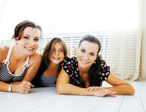Mature sisters twins at home with little daughter, happy family Stock Photo