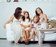 Mature sisters twins at home with little daughter, happy family Stock Photos