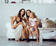 Mature sisters twins at home with little daughter, happy family Stock Photography