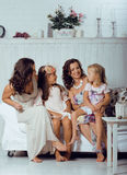 Mature sisters twins at home with little daughter, happy family Royalty Free Stock Photography