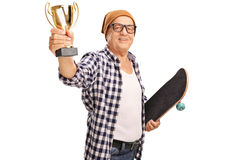 Mature skater holding a golden trophy. Mature skater holding a skateboard and a golden trophy isolated on white background Royalty Free Stock Images