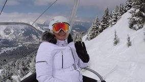 Mature Skier Climbs Up The Chair Lift To The Mountaintop And Wave Her Hand. Happy mature woman skier or snowboarder climbs up the mountain sitting in the chair stock video footage