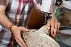 Mature skilled workman sewing leather boots on stitch lathe Stock Photo