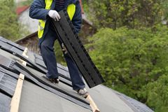 Workman install tile on roof of new house under construction stock photo
