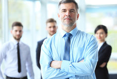 Mature smiling business manager crossing his arms in front of his business team. Royalty Free Stock Photos