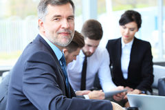 Mature smiling business manager in front of his business team. Royalty Free Stock Photo