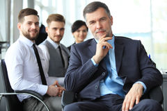 Mature smiling business manager in front of his business team. royalty free stock images