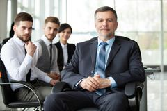 Mature smiling business manager in front of his business team royalty free stock image