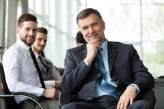 Mature smiling business manager in front of his business team stock images