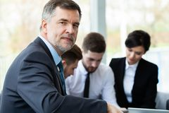 Mature smiling business manager in front of his business team stock photos