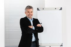 Mature smiling businessman making presentation on flipchart. Stock Photos