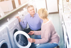 Mature smiling couple choosing home washing machine Royalty Free Stock Image