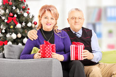 Mature smiling couple sitting on a couch and holding gifts at ho Stock Image