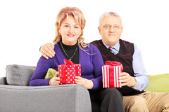 Mature smiling couple sitting on a couch and holding gifts Royalty Free Stock Photography