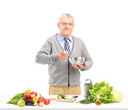 Mature smiling gentleman preparing a fresh salad Stock Photography