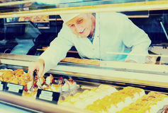 Mature smiling man selling tasty confectionery products. On counter of bakery Stock Images