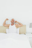 Mature smiling man stretching arms in bed Stock Photo