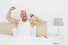 Mature smiling man stretching arms in bed Stock Images
