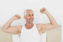 Mature smiling man stretching his arms in bed Stock Photo