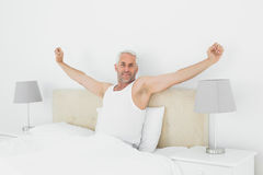 Mature smiling man stretching his arms in bed Stock Photography