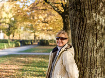 Mature, smiling woman in autumn park at tree Stock Images