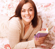 Mature smiling woman brunette with book at home Royalty Free Stock Photo