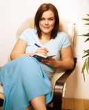 Mature smiling woman brunette with book at home Stock Photo