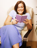 Mature smiling woman brunette with book at home Stock Photos